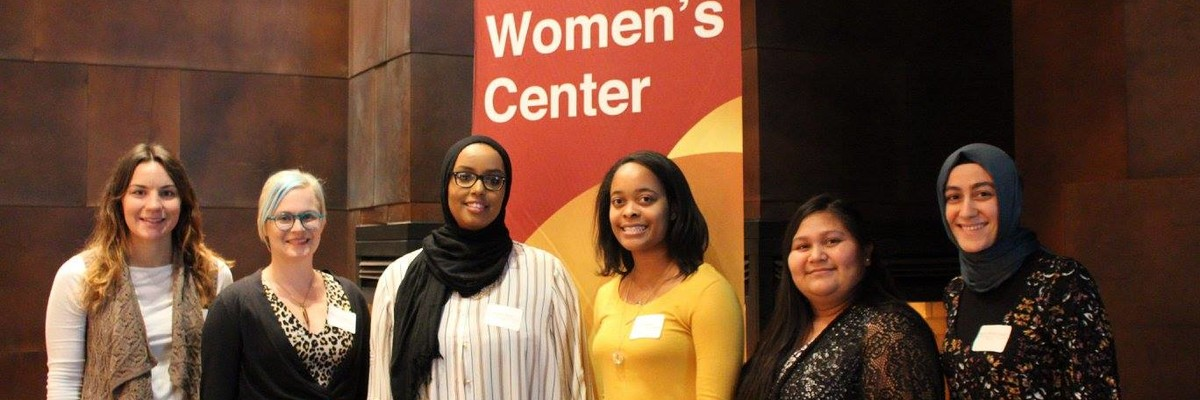 "Six students stand in a row, facing the camera and smiling. Behind them is a maroon and gold banner that reads ""Women's Center""."
