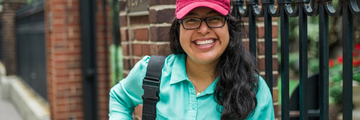 A scholarship recipient smiles for the camera. She has dark wavy hair and glasses, wearing a blue shirt, with a backpack on her shoulder. She wears a maroon baseball cap that says FEMINIST in gold letters.
